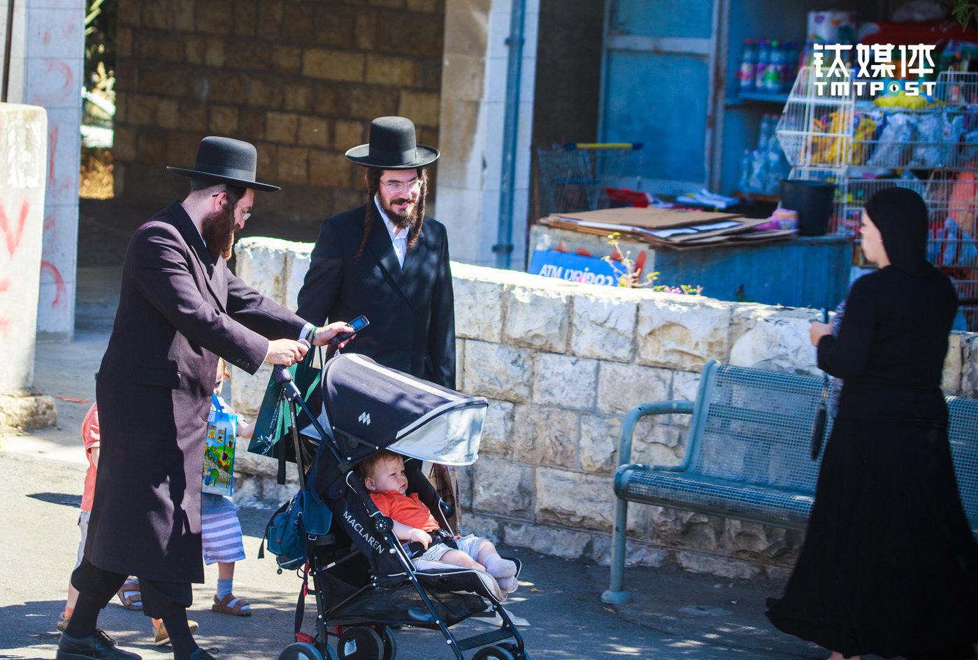 两位身穿黑色正装、礼帽的正统犹太信徒与一位穆斯林妇女擦肩而过。耶路撒冷作为犹太教、基督教和伊斯兰教的三教圣地,融合三教信徒在这里共同生活。(图/朱玲玉)