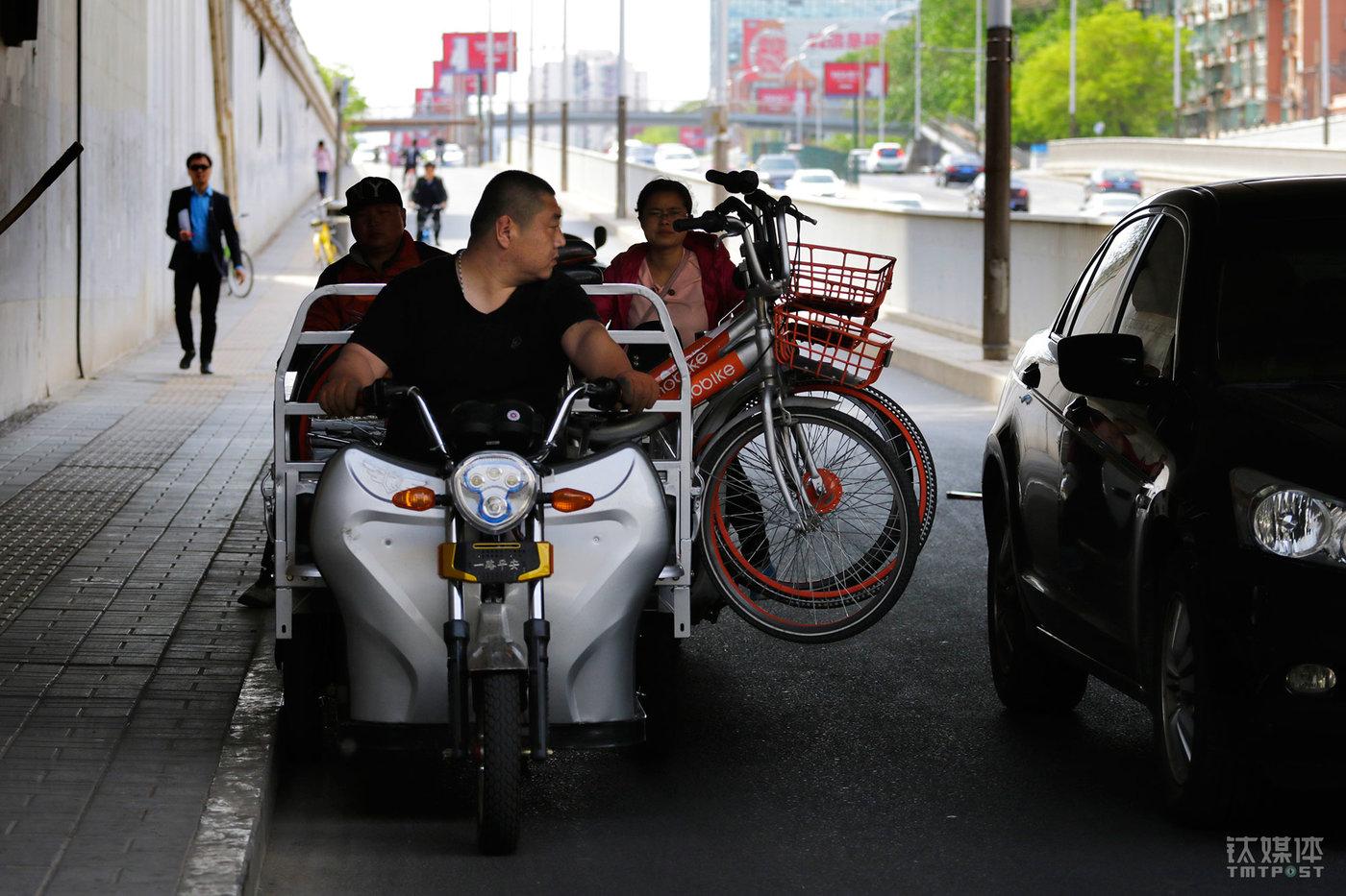 """载着单车经过一辆停靠的小汽车,大强放慢速度,回头紧盯着自己与小车的距离。行车路上,因为单车的前轮挂在外面,他最怕剐蹭行人和车辆,因为""""这个三轮没有保险,万一发生刮擦挺麻烦""""。"""