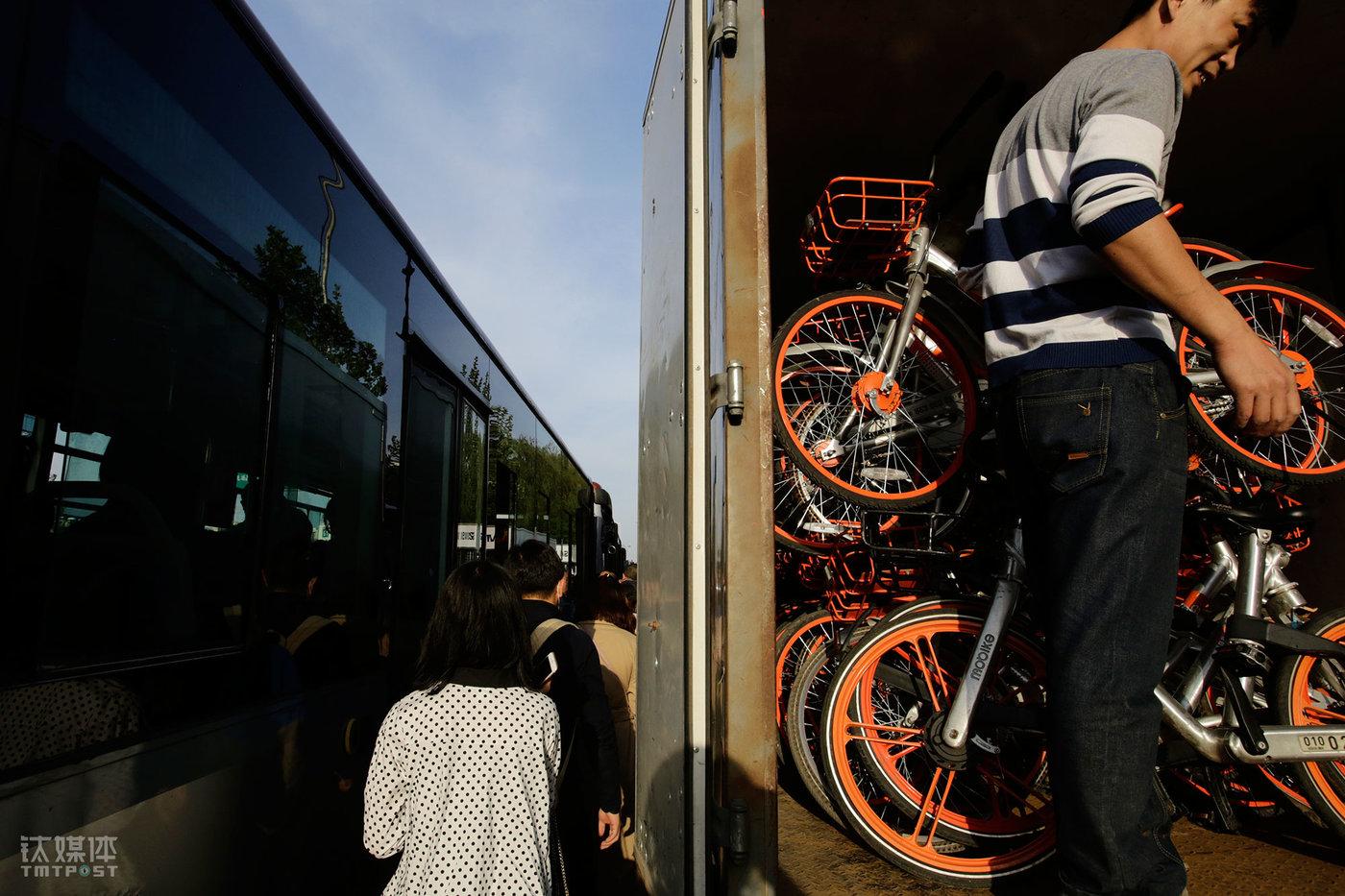 八王坟东公交站,厢货装满车单车准备关门,一辆公交车停靠在一旁,赶车的人从两辆车中间排队穿过。