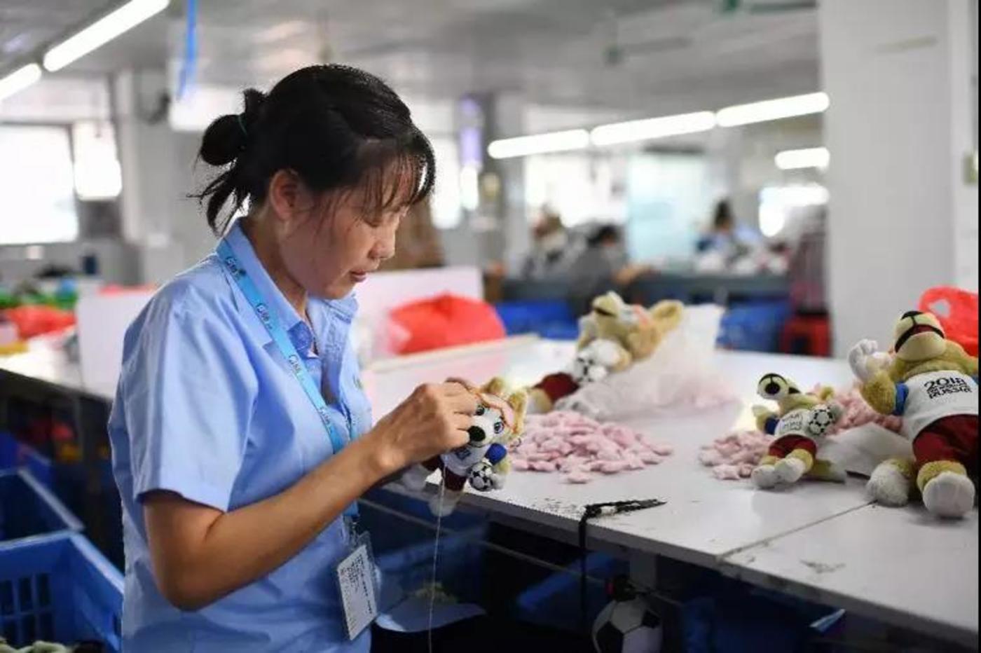 """刘爱敏在车间手工缝制世界杯吉祥物。中国10个省30多家制造商,与数千名缝制女工一起,在阿里巴巴的数据筛选和匹配下,成为""""Made in Internet(互联网制造)""""这个最新概念中的一环。(梁清 摄)"""