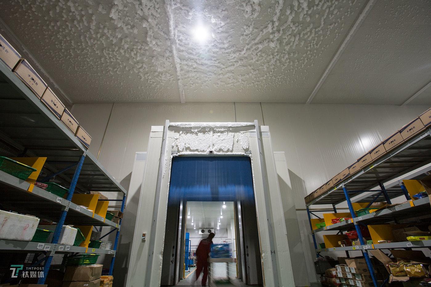 -18℃的冷冻区和5℃的冷藏作业区之间有一道感应门,拣货员从冷冻区完成订单拣选后用小车将商品推送到冷藏区供复核、打包。冷热空气交汇使得冷冻区大门的门楣和天花板上覆盖上了冰雪。