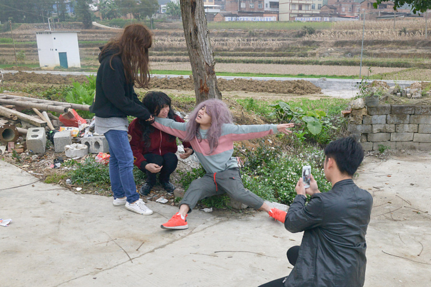 快手红人蹲在树下拍段子,图片来源@视觉中国