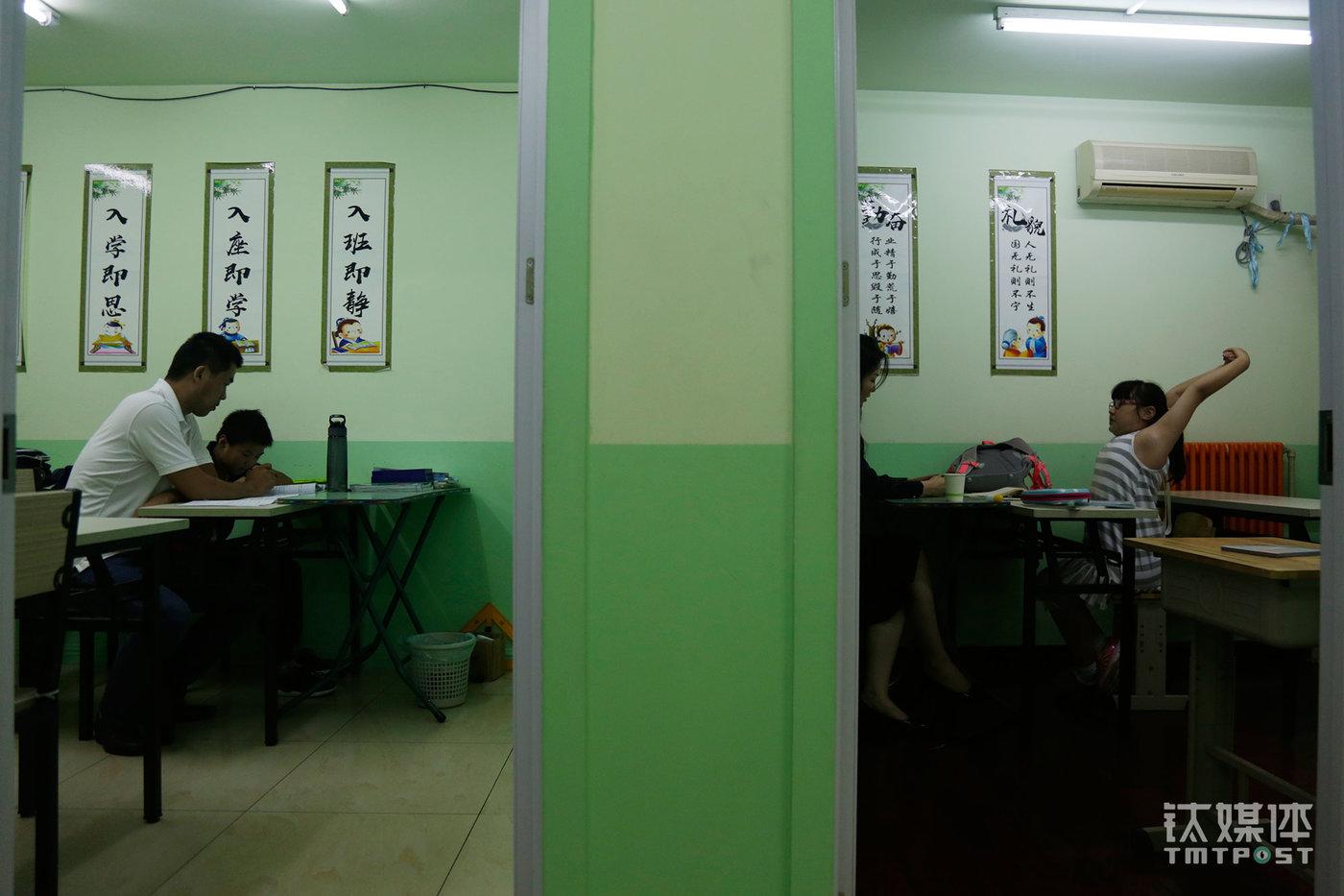 """两名老师在给两名放学后来上课的小学生讲题。这家培训学校与被称为""""北京最牛小学之一""""的中关村一小仅一墙之隔,在这个面积不大的小区,有""""超过40家""""各类针对小学生的培训学校。(陈拯 摄)"""