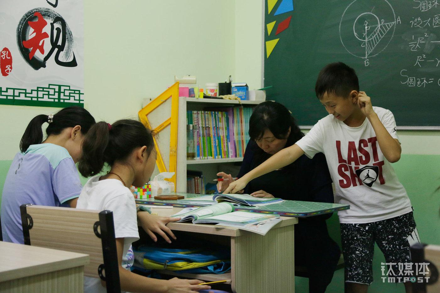 """一个小班上,几名六年级孩子在解答奥数题。这里以一对一和小班为主,针对小升初择校开办的奥数课是周老师教授的主要内容。周老师向钛媒体《在线》介绍,海淀区名校的小升初择校奥数的比重很高,是拉开学生之间差距的主要原因,""""六年级孩子要学到初三的数学水平才有机会胜出""""。"""