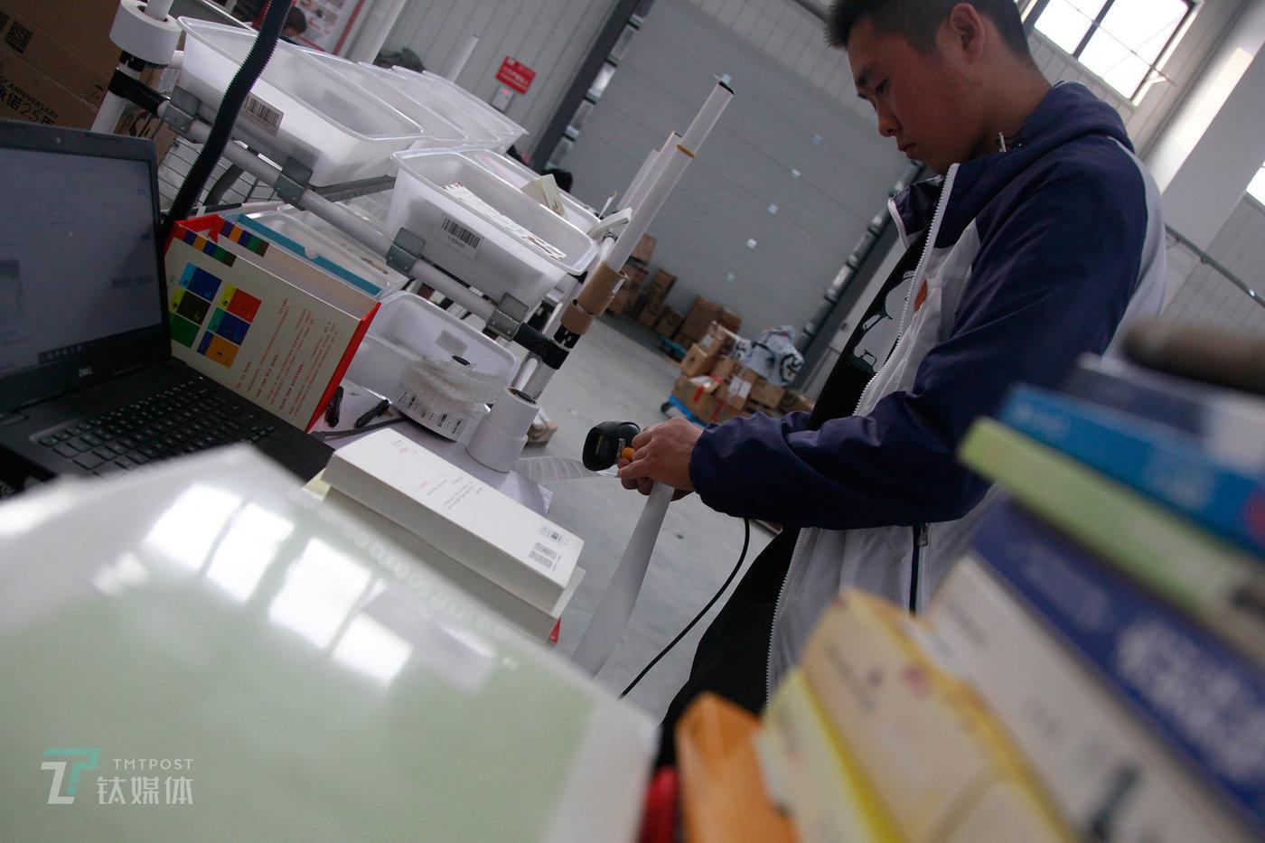 用户寄到多抓鱼工厂的书在拆包后,要经历的第一个环节就是在点货区贴抓码。