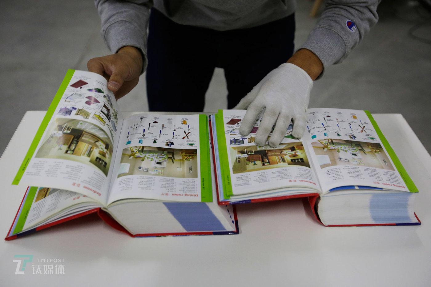 """杨玉擎的同事在对两本词典做正盗版鉴定。他们总结了盗版书的五个通用特征:书的腰封印在封面上;外文书封底有中文书名或中文拼音;封案连着扉页,书没有前衬页和后衬页;直接印着""""XX全集""""字样或把套装书缩印成一本;平装绘本定价高于20元。(陈拯 摄)"""