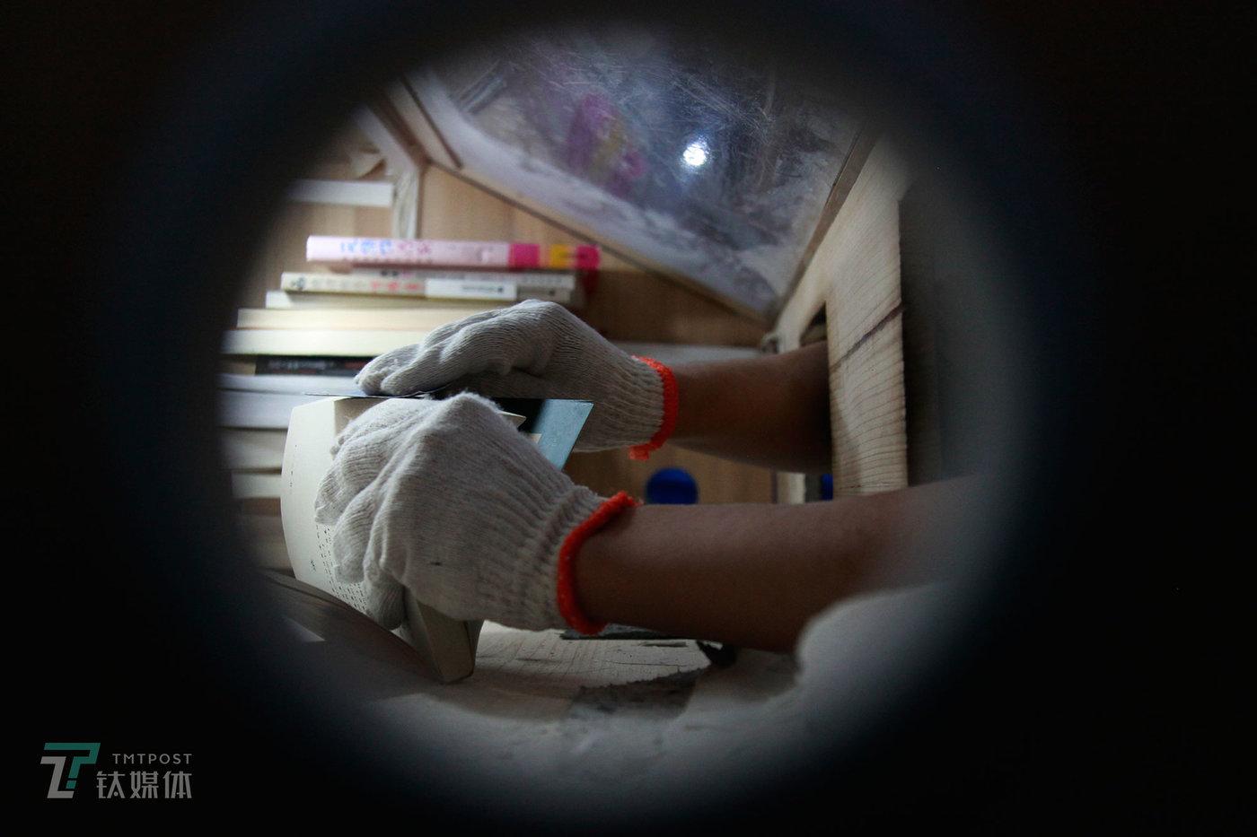 打磨是在一个封闭的工作台内进行,工人使用的工具是砂纸。