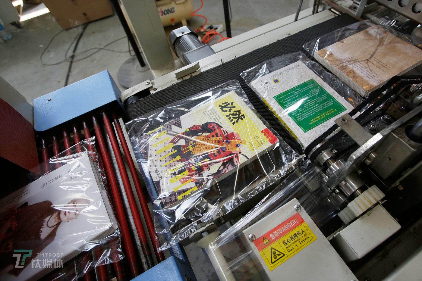 消毒完毕的书会被送上塑封机进行包装,这也是一本二手书在多抓鱼翻新工厂经历的最后一道工序。(陈拯 摄)