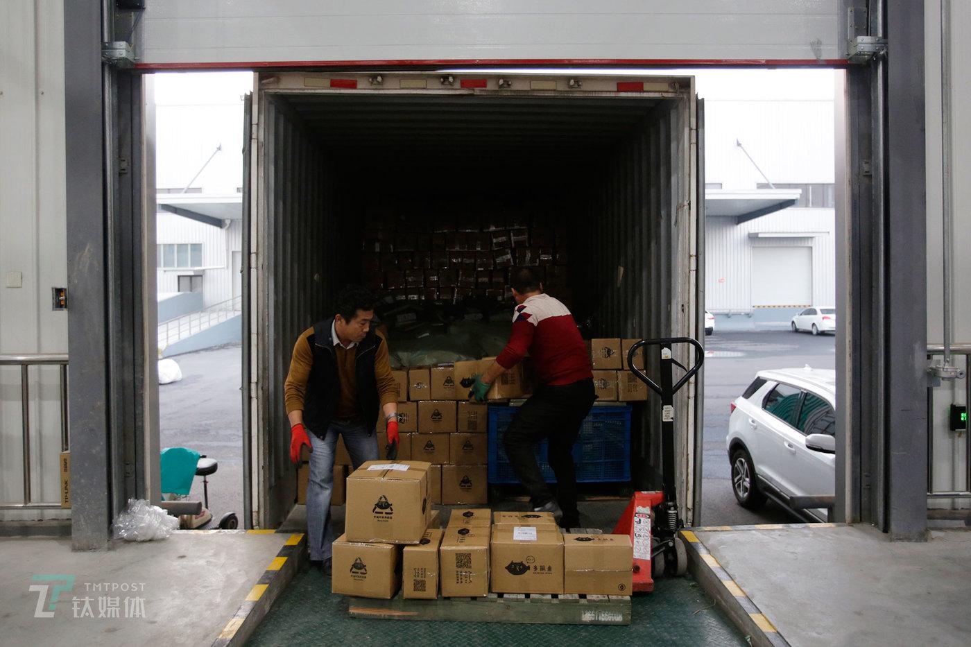 """即将被送往全国各地的二手书包裹,正被装上货运车。多抓鱼上线一年半,收购二手书130万本,卖出100万本。2018年国庆假期,多抓鱼地下书店也对外营业。""""不久我们就会对工厂进行自动化改造。""""一名负责人介绍,到时候会邀请用户到我们工厂来亲自体验二手书的翻新之旅。(陈拯 摄)(图文/孙林徽 编辑/陈拯 视频/Tolocam)"""