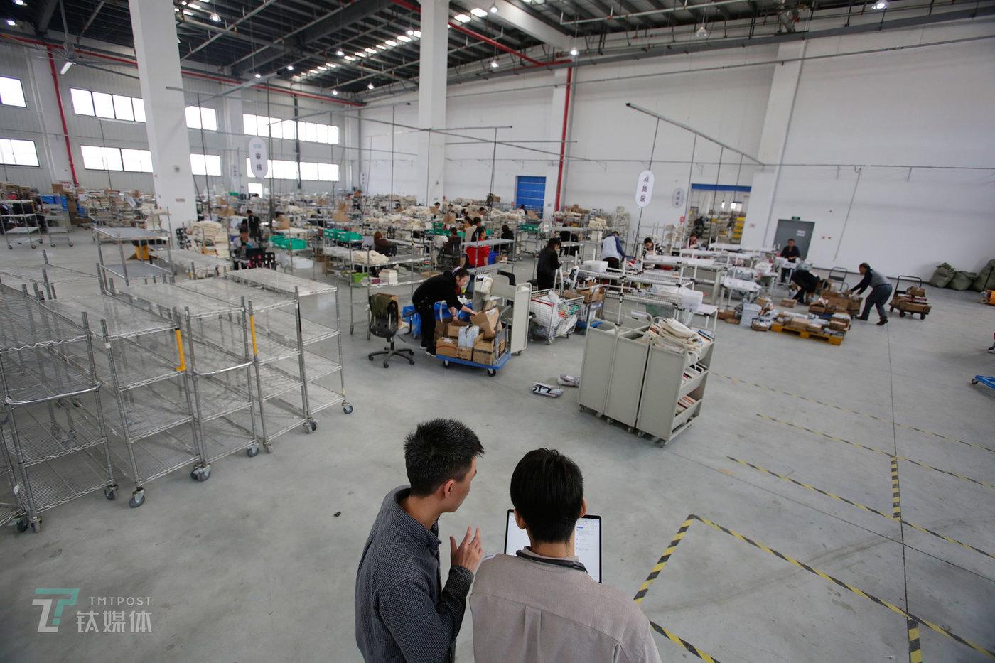 2018年10月17日,天津市武清区多抓鱼翻新工厂,两名工作人员在探讨流程的优化问题。这家占地七千多平米的工厂,就是二手书翻新的核心地带。