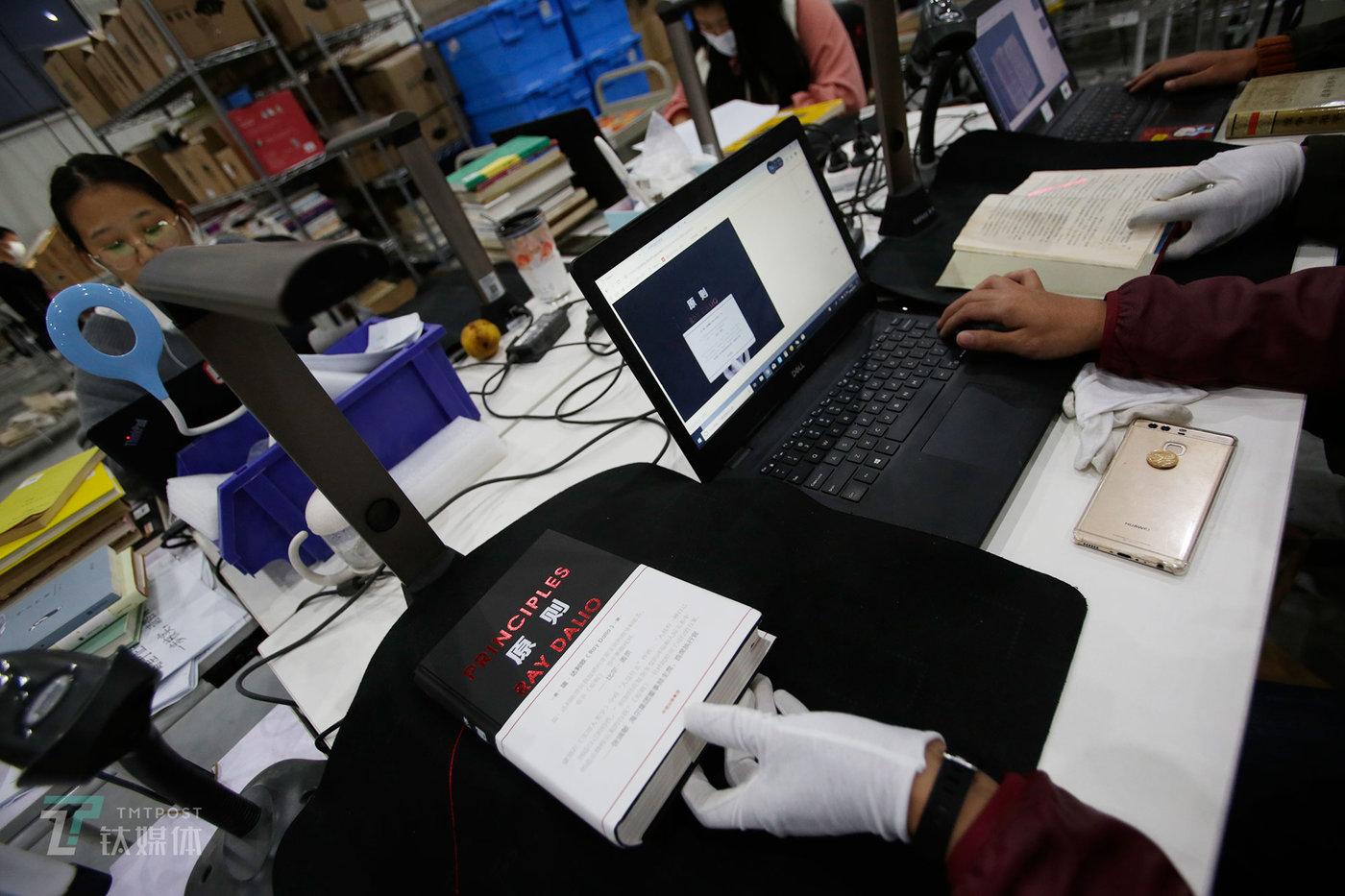 """工作人员在为一本被拒的二手书拍照,并填写拒书理发送给卖书用户。有4%-5%的书会被多抓鱼拒掉,这中间有一半是盗版,其他的则是因为""""缺册""""或""""品相过差""""。被拒掉的书,会在这家工厂仓库保留48小时,若卖书用户要取回图书,需要自行承担邮费(用户寄送的邮费由多抓鱼承担);若是所寄的二手书通过审核,用户在48小时内就能收到多抓鱼支付的书款。"""
