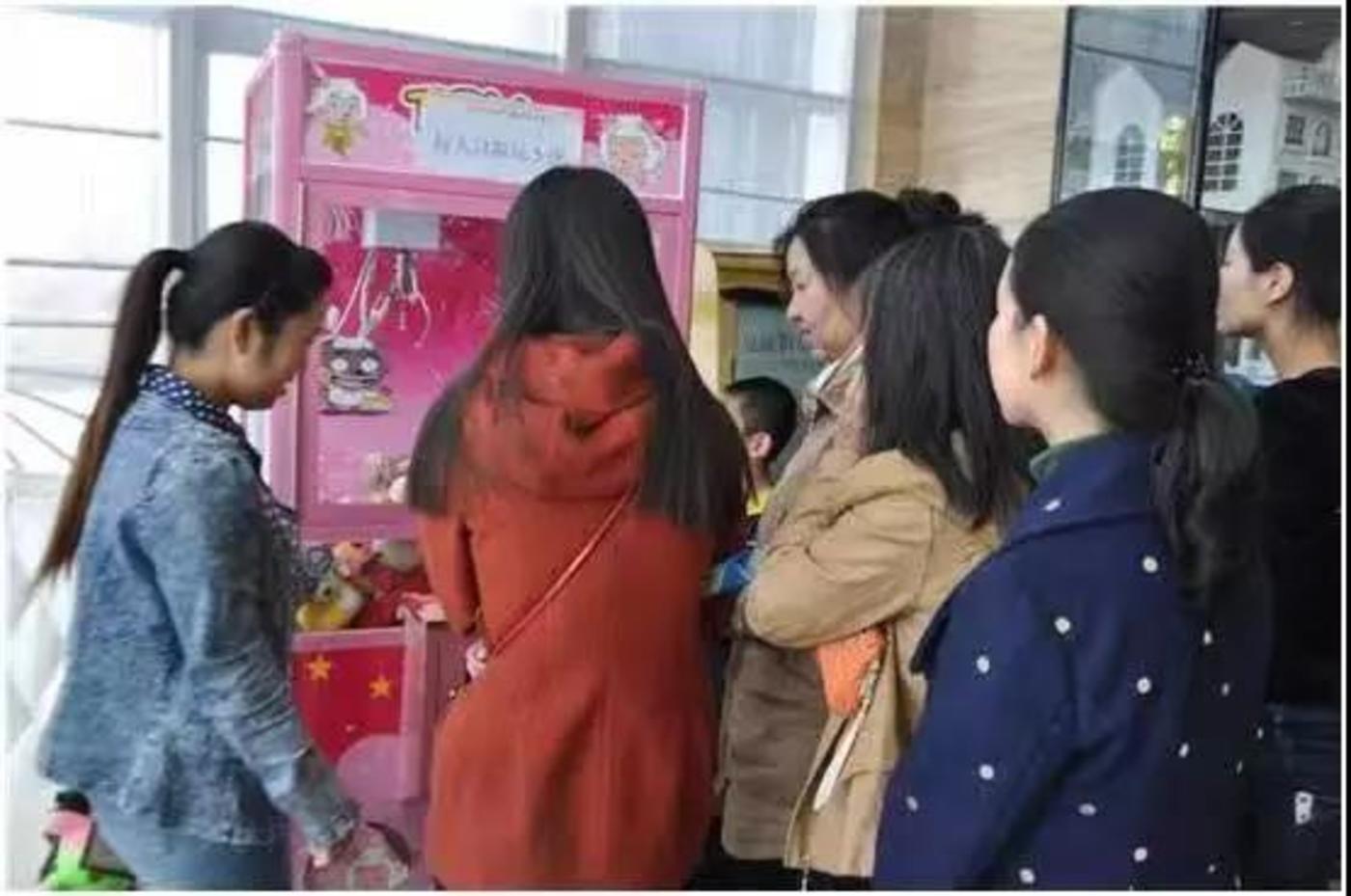 在影院娃娃机前排队的顾客