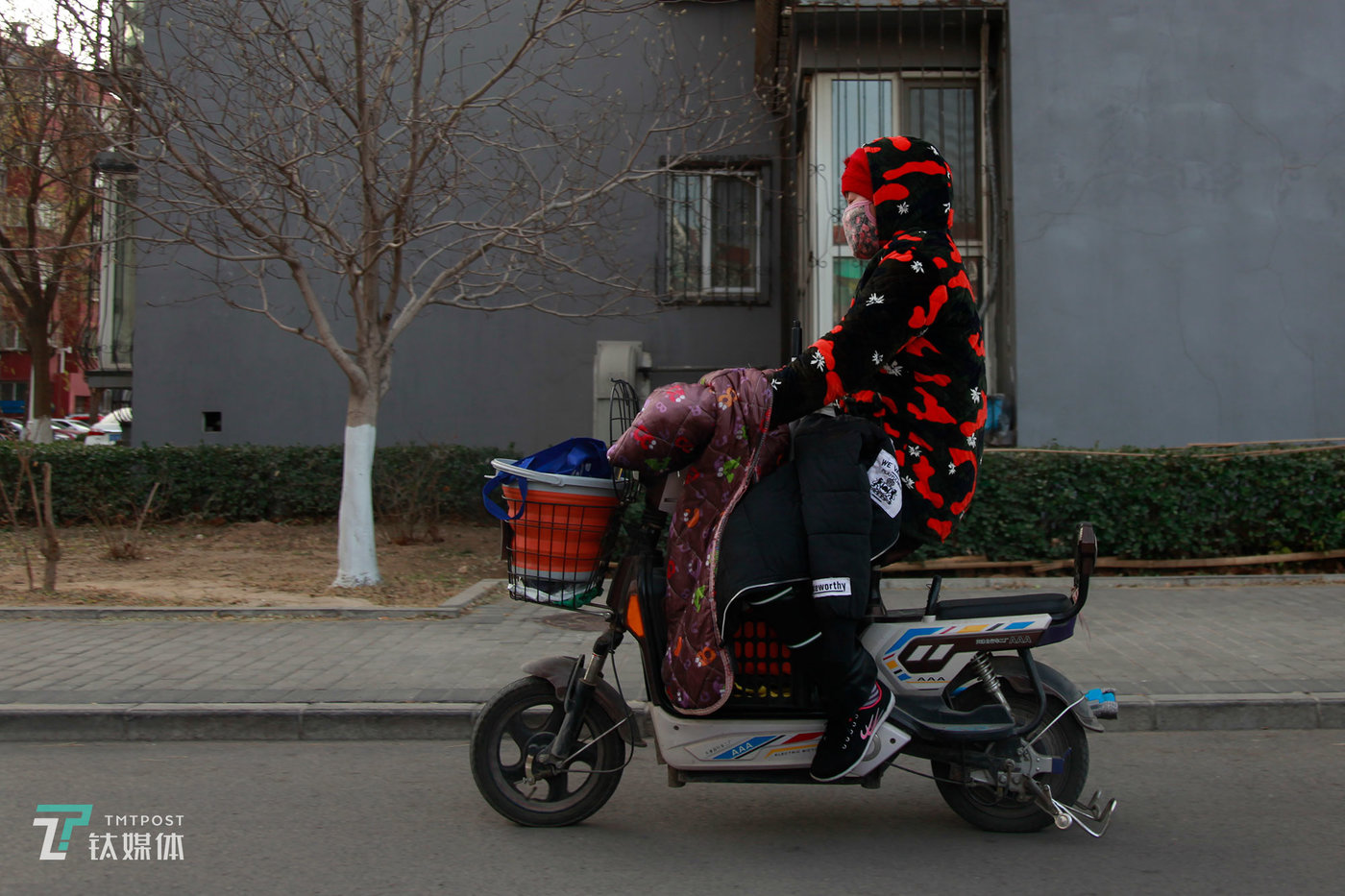 """夏芸骑电动车赶往租客家。这是她的第二辆车,前一辆丢了,丢的时候她正在给租客做清洁,""""当时急冲冲地上楼干活,怕错过时间,忘了锁车。""""北京的冬天一度达到零下8度,夏芸在工作服外套了两件棉袄,在腿上加了一个护膝把自己全副武装起来。尽管冬天很冷,夏芸还是最喜欢在冬天干活,因为夏天打扫流汗太多,有时候眼睛都睁不开,清理垃圾的时候经常有成群的蚊虫打到脸上。"""