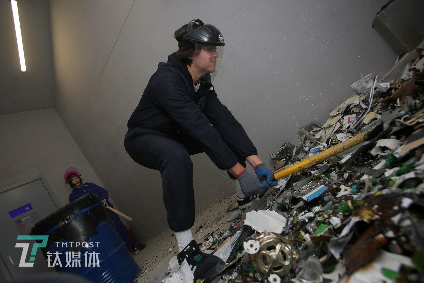 一位澳大利亚来的游客在砸完自己筐里的瓶子后觉得不太过瘾,继续抡着棒球棍在面前的碎片里猛砸。