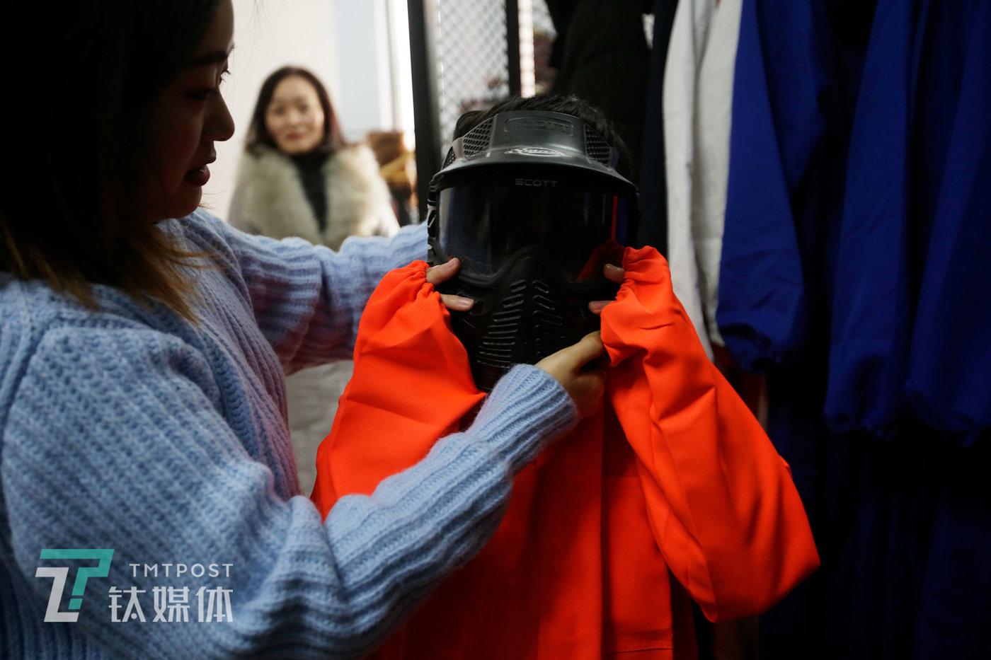 一名12岁的女孩在店主的帮助下戴上防护头盔。她和同学看了抖音博主短视频后,约着过来玩的。
