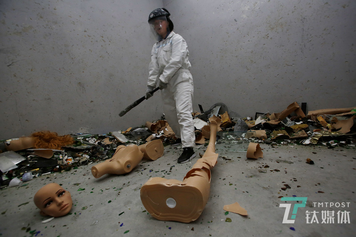 """A female customer holds an iron bat, ready to smash an already disintegrated mannequin. She came with three female colleagues for release and smashed several baskets of bottles and a mannequin. """"She has had the blues recently,"""" a friend of her told TMTPost Image."""