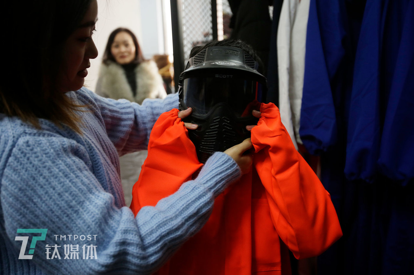 A 12 year old girl puts on a protective helmet with the help of the shop owner. She and her classmates came together after viewing some short video clips on the popular short-form video app Douyin, which is named Tik Tok outside China.