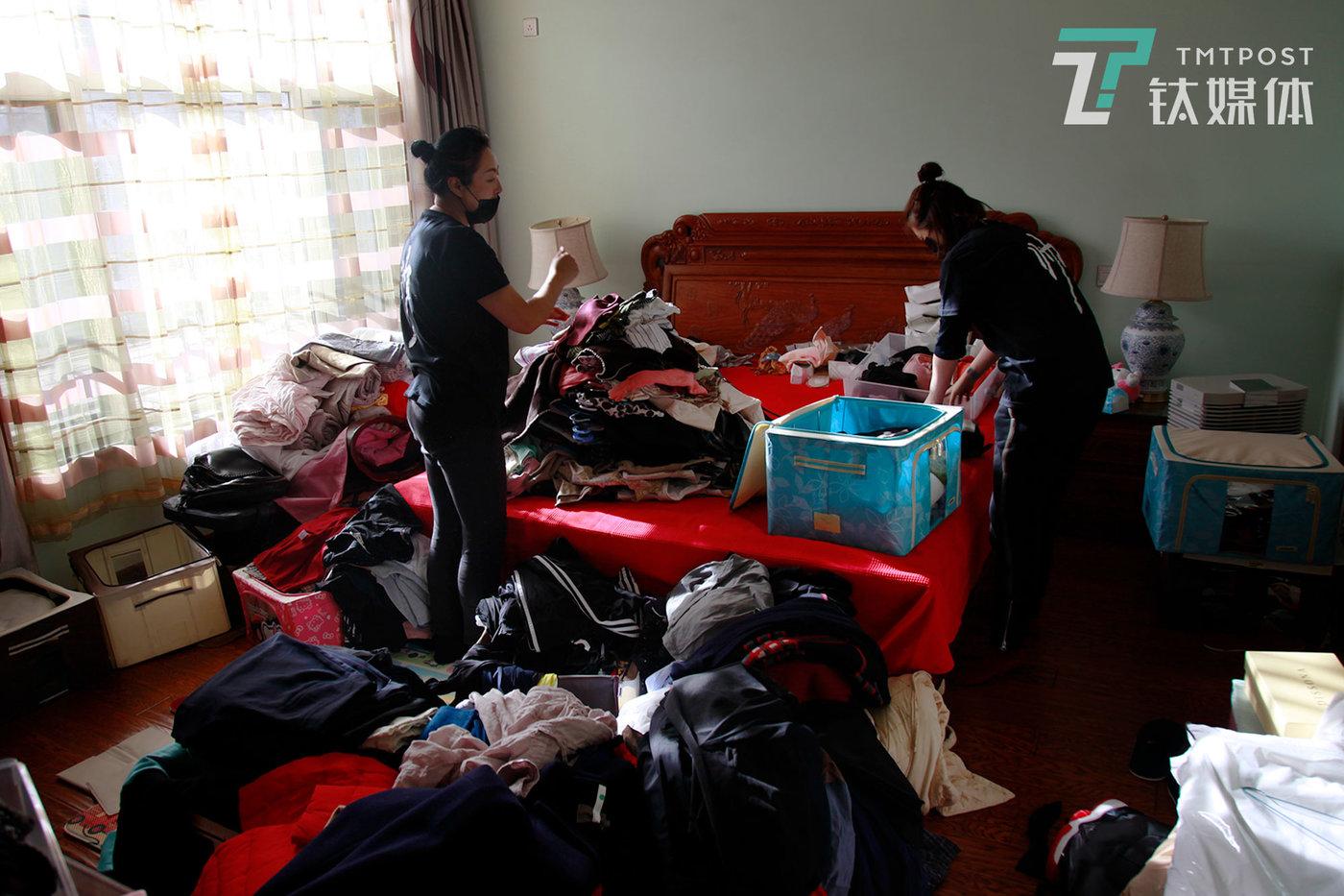 整理师将房主衣服全部从衣橱拿出来,堆放在床上。