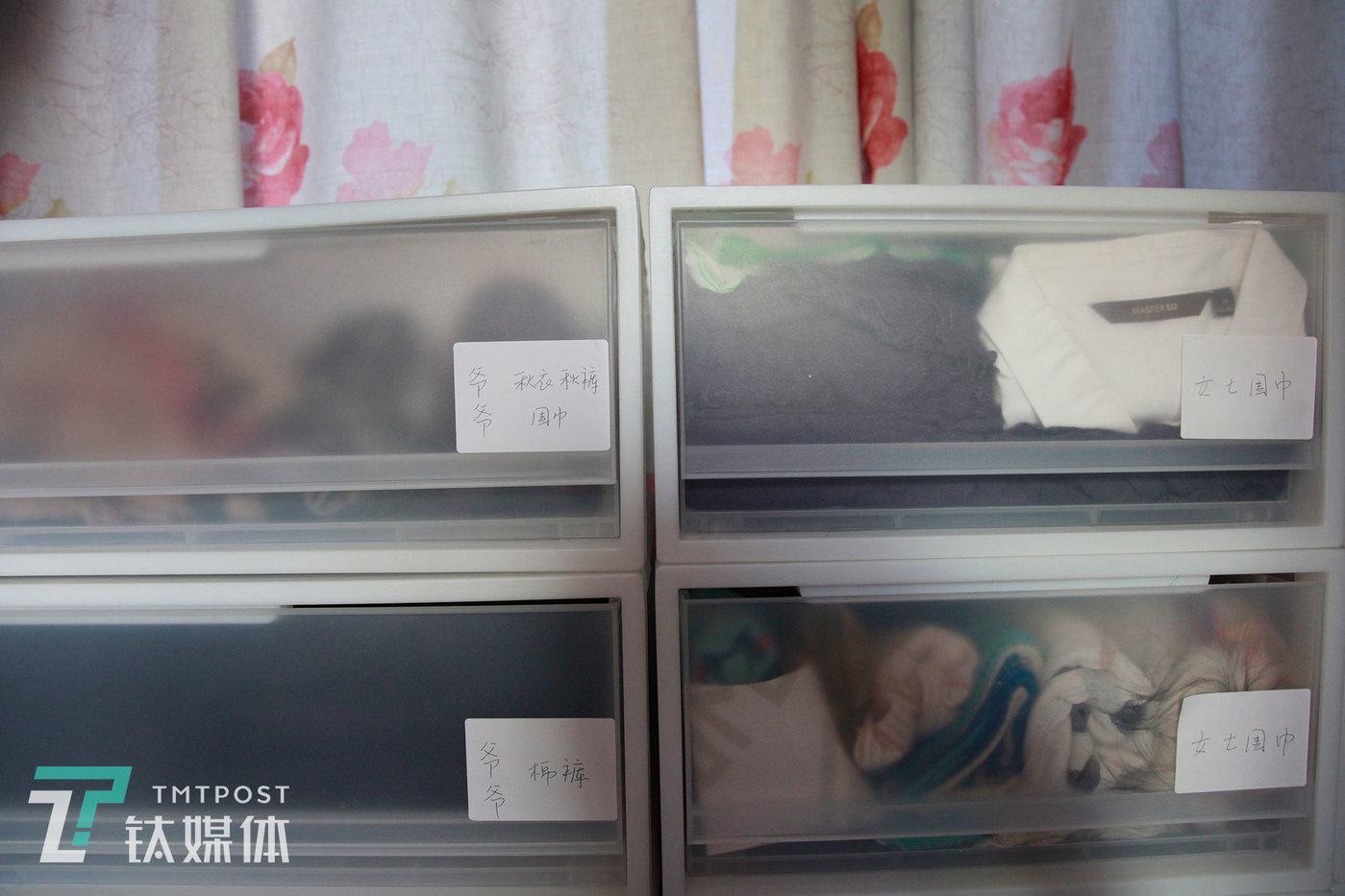 邵帅将房主不常穿的衣物放进收纳箱里并用标签纸标记。