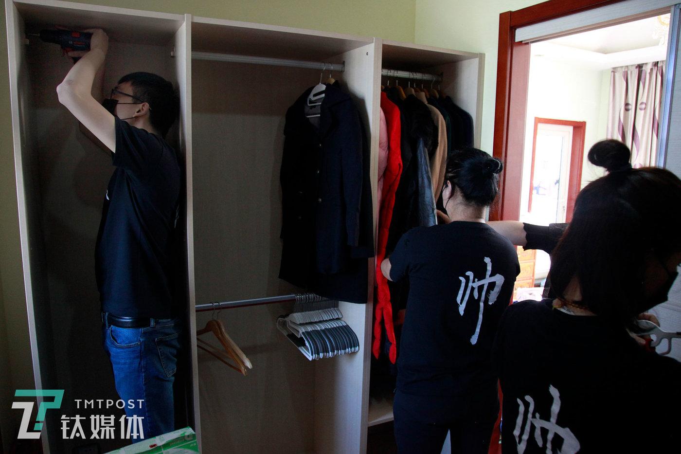 邵帅衣橱管理团队成员尹阔(左)正在对衣橱进行内部改造,其他伙伴则在一旁整理衣服。