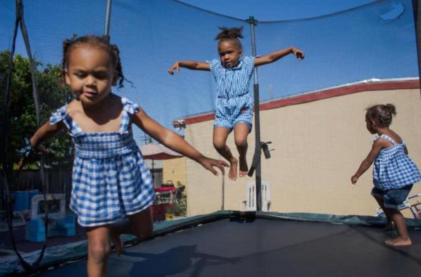 阿莫·雷·斯坦利(Armore'Ray Stanley,中)和她的侄女们在东帕洛阿尔托的后院玩耍。自从斯坦利的母亲帕特丽夏·卡特(Patricia Carter)在2003年买下这栋房子以来,其价值已经翻了一番多。但是如果卖了它,斯坦利就负担不起在这个地区居住的成本