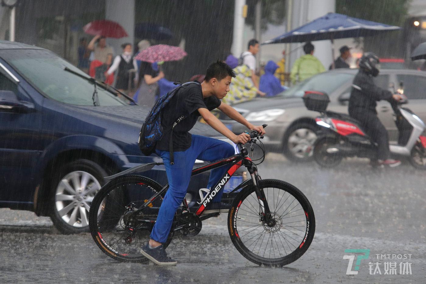 """【雨中""""沉思""""】6月12日下午,北京,突如其来的大雨让人措手不及。一名冒雨骑行的学生在等待红绿灯时,仿佛陷入了沉思。"""