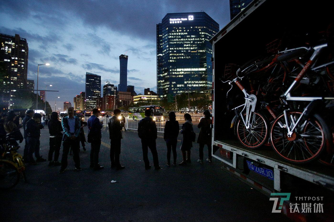【归途】4月23日晚,北京CBD八王坟公交站,等待去往燕郊班车的上班族和即将被运走的摩拜单车。