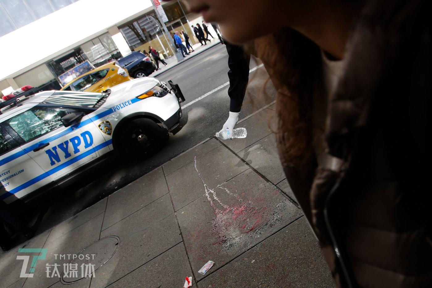 【NYPD】10月20日,美国纽约曼哈顿街头,一起持刀抢劫案现场,警察用矿泉水清洗伤者留在地面的血渍。