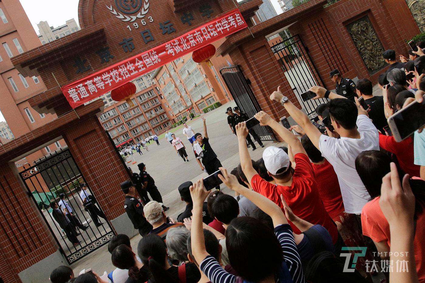 【Victory】6月8日下午,北京日坛中学,高考最后一科结束后,第一个走出考场的考生向校门外等候的家长打出胜利的手势。
