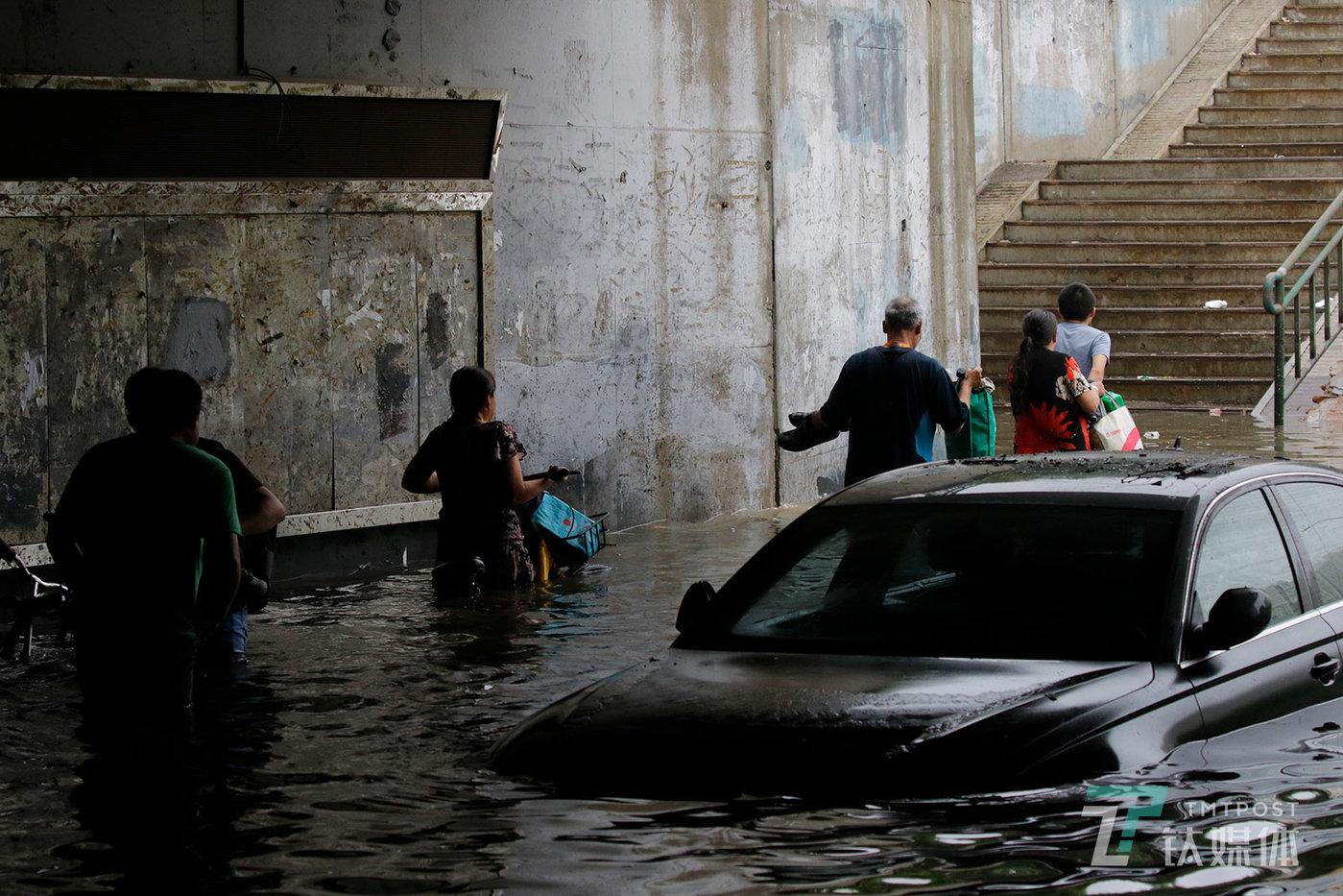 【蹚水】7月16日,北京昌平区回龙观育知东路城铁桥下,强降雨后形成了最深超两米的积水,行人涉险蹚水穿过桥下的人行道。