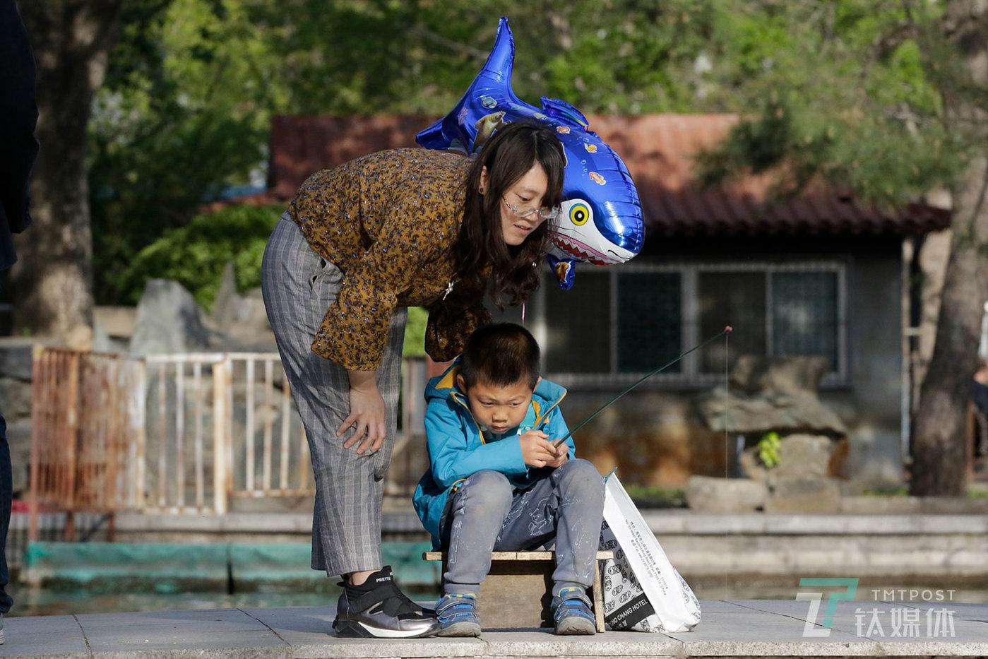 【钓鱼】4月15日,北京日坛公园,一位母亲陪孩子钓鱼。
