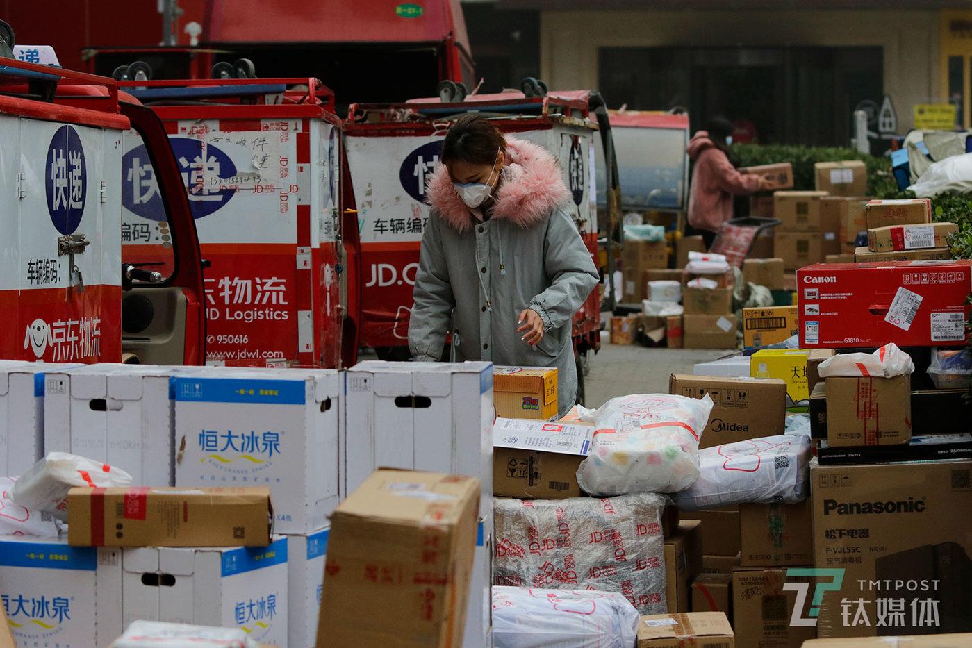 【爆仓】11月14日,雾霾来袭,北京东大桥京东物流站点外,工作人员在整理双十一的包裹。