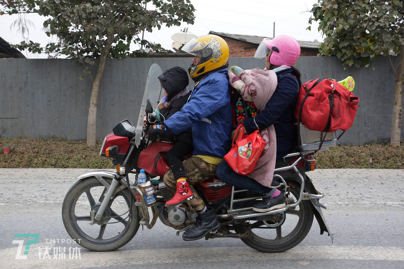 1月26日9:17,广西梧州321国道,骑行回家的一家人。