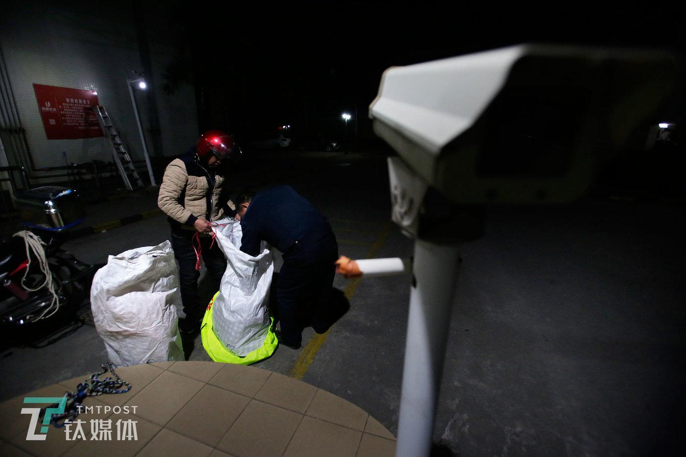宿舍大门,值夜保安检查苏宏杰的行李。工人携带大件行李物品出宿舍区,都要接受这样的例行检查。
