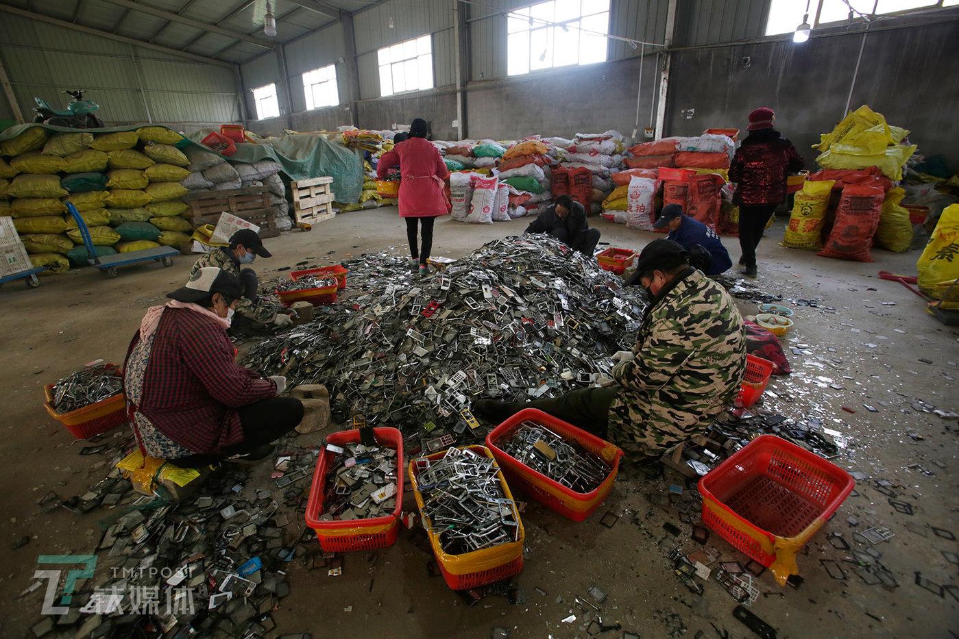 拆解厂内,几名工人在处理手机金属外壳,他们的工作是用锤子把外壳上的塑料屏保敲下来。这些金属壳会被专门的收购商买走用于提炼锌。