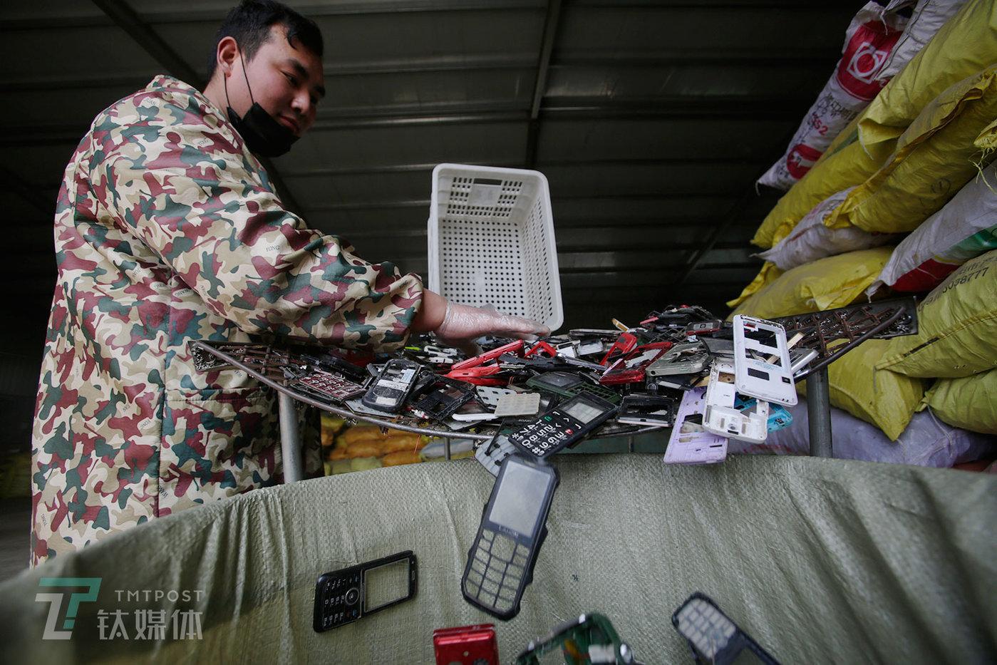 一名工人在筛选塑料手机壳,这些手机壳会被当做废塑料卖掉。这家拆解厂是一个关键的集散地,上游整机回收商将手机送到这里,下游零件收购商再从这里买走各个零部件提炼金属或再利用。