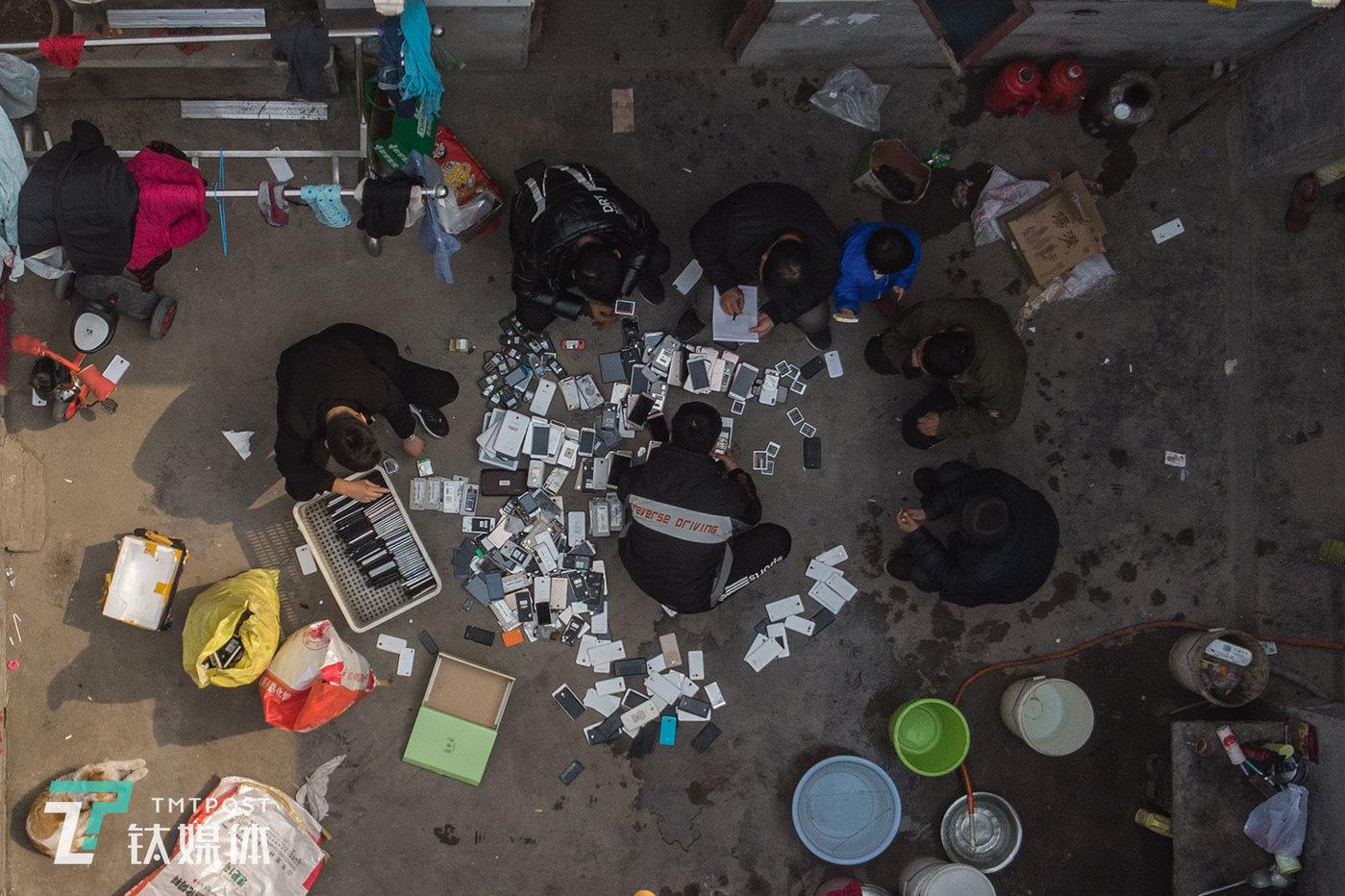 """西房庄村农户老陈家,废旧手机回收商李蒙(中)在清点旧手机。李蒙从60公里外的地方开车赶来收货,他是临沂地区规模最大的回收商之一,每年经手的货有""""两千多万人民币""""。"""