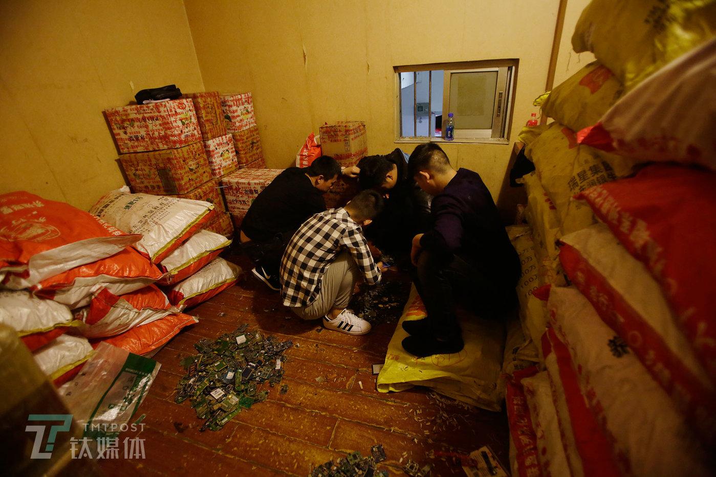 """2月26日,买卖双方在一间摆满货物的房间看一批手机主板。房间编织袋和纸箱装着的货""""大约价值一百多万""""。"""