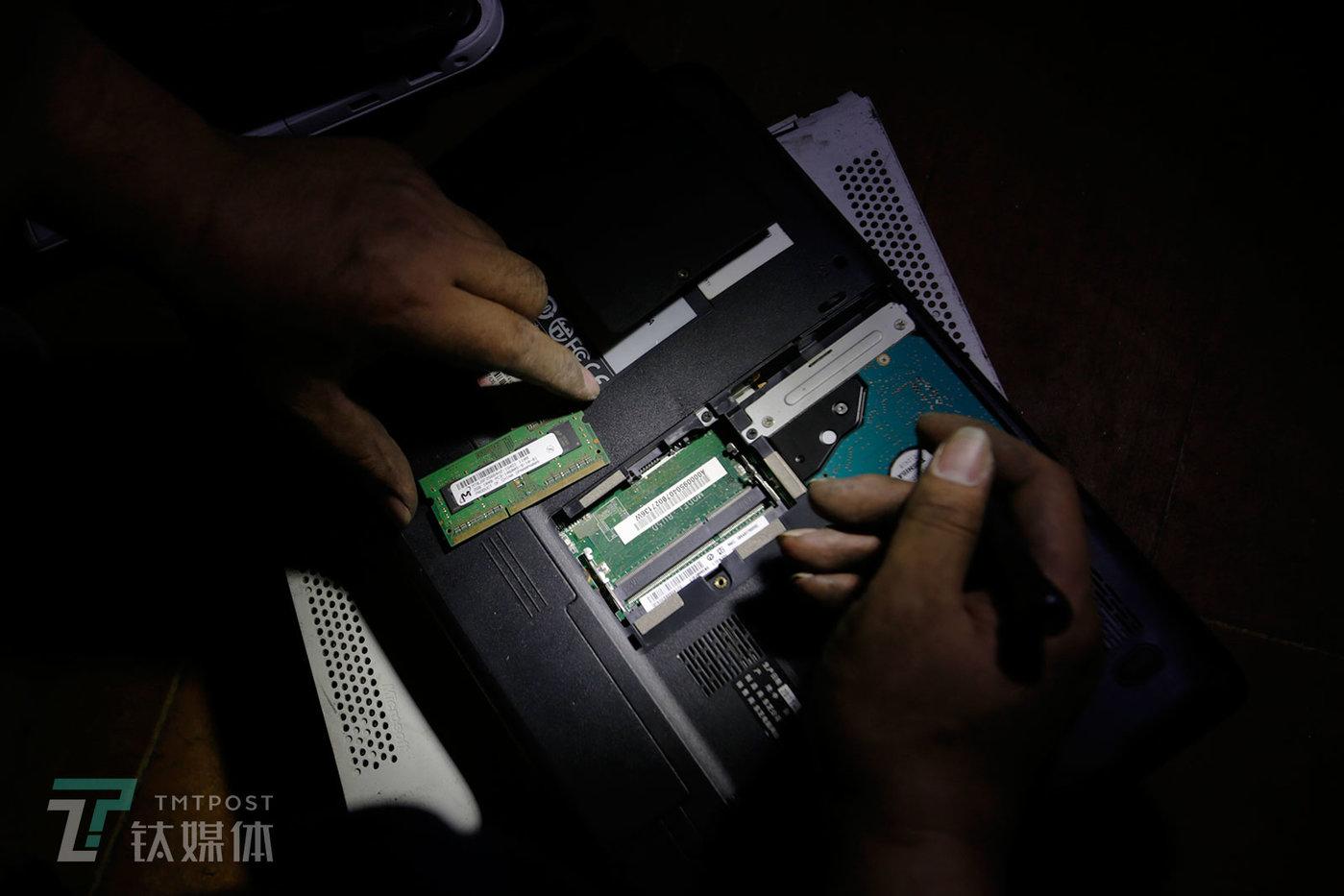 一位笔记本买家拆开一台废旧笔记本后盖检查配置。除了屏幕,内存条和硬盘的配置是决定一台废旧笔记本价格的重要因素。显然,深圳的买家对笔记等3C产品的熟悉程度和鉴别真伪的能力,远远超过全国各地涌来的卖家们。