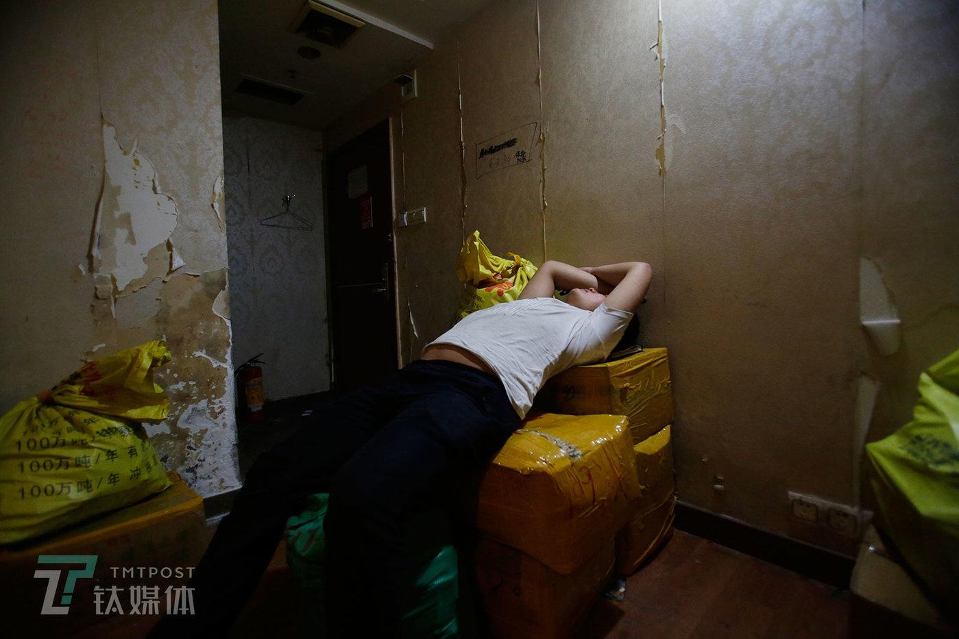 送走客户,一名来自山东的卖家躺在几箱手机上打起了盹。