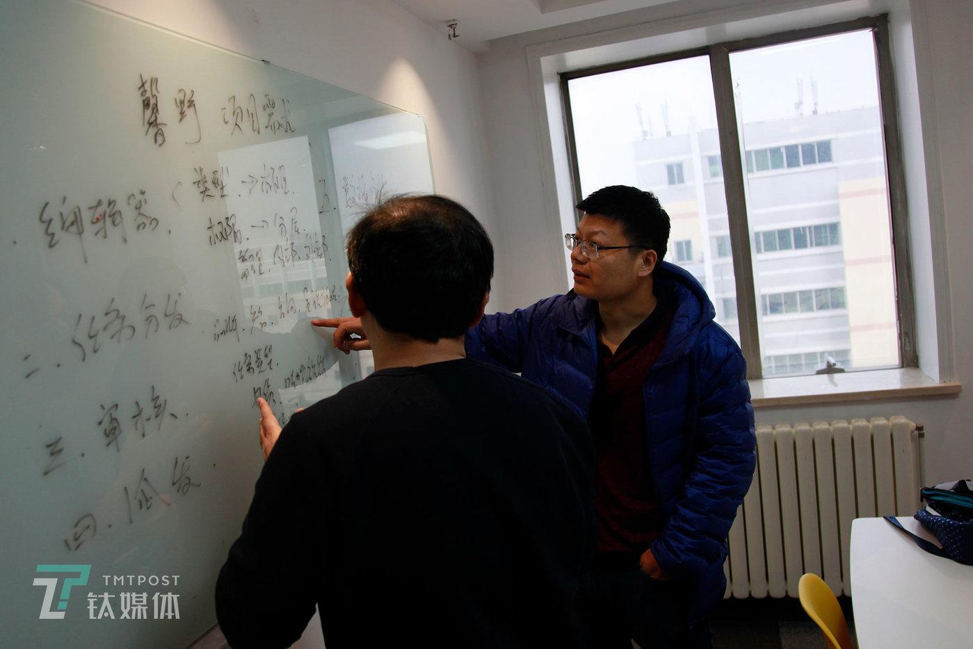 3月8日,北京,被裁失业后自主创业的陈明(右)在客户会议室跟客户讨论需求。