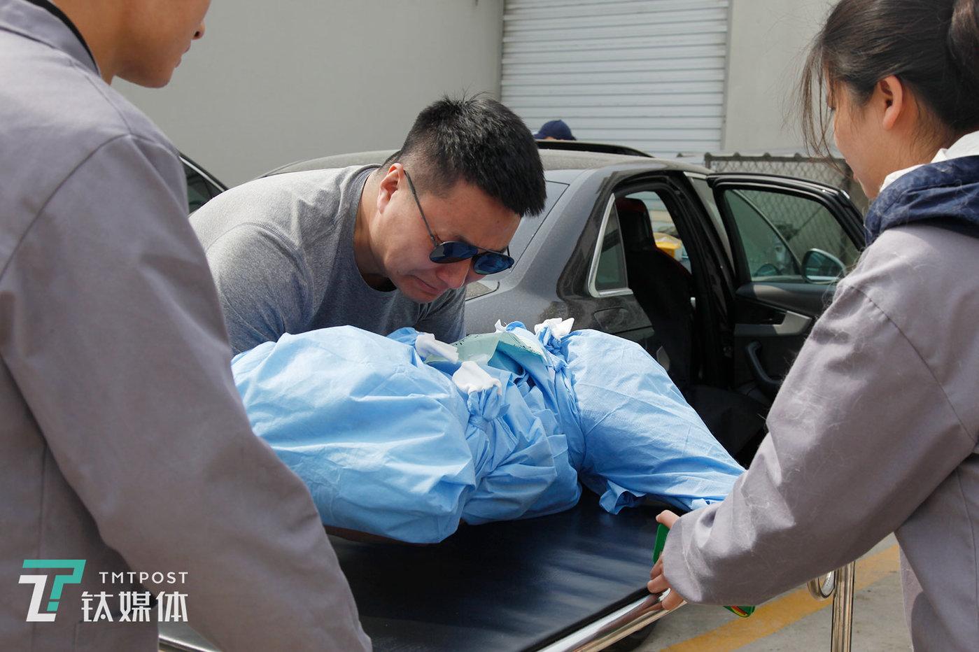 """3月19日下午,北京,狐狸(化名)将爱犬""""馒头""""的遗体从车上抱下,放置到手推车上。"""