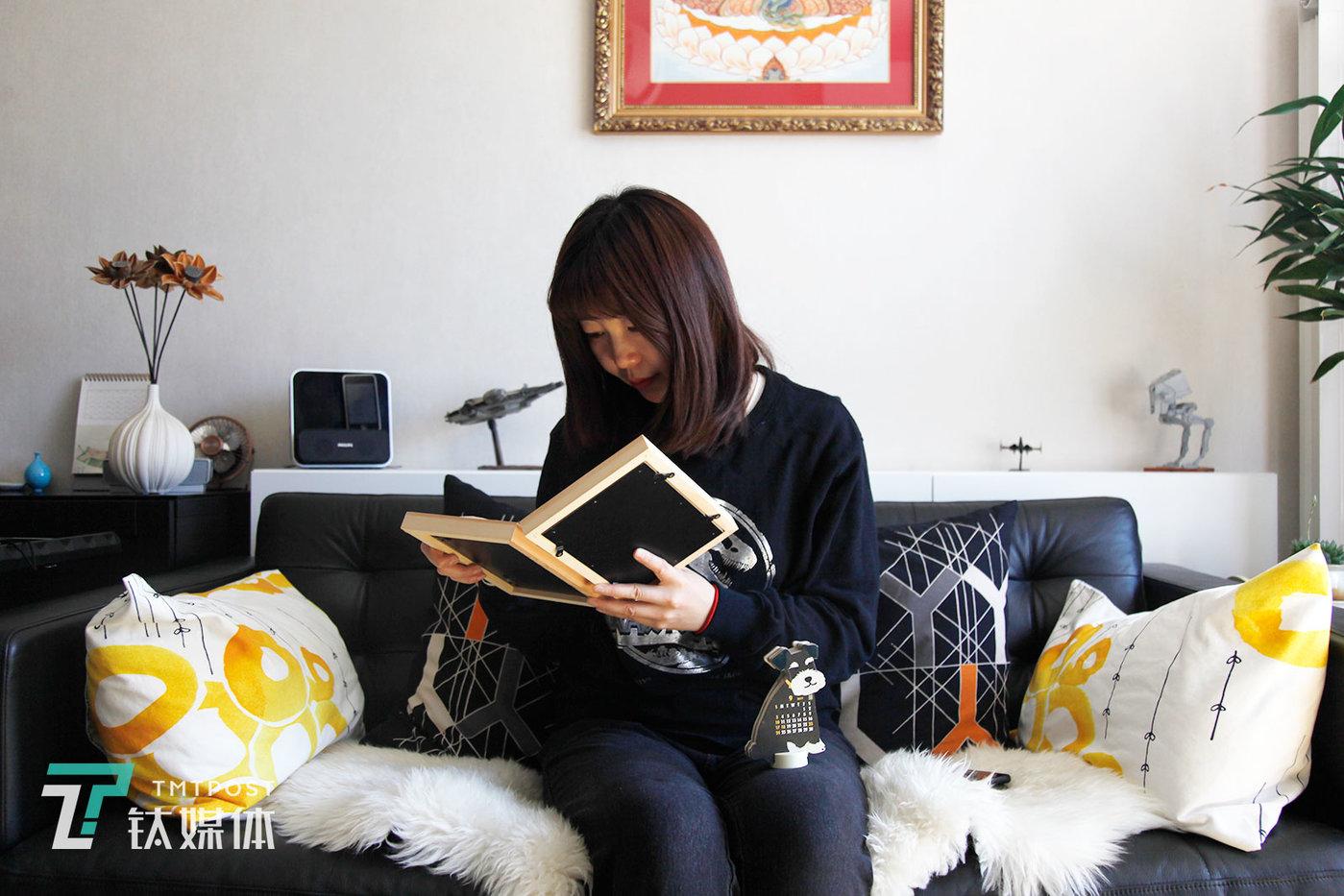 """3月23日,北京丰台,北北(化名)坐在沙发上看着爱犬纳瑞的照片。纳瑞是一条雪纳瑞犬,在北北家生活了11年。纳瑞是朋友送给北北的礼物。""""它来的时候刚一个多月,还没有毛绒玩具大,是我从怀里揣着带回来的。"""""""
