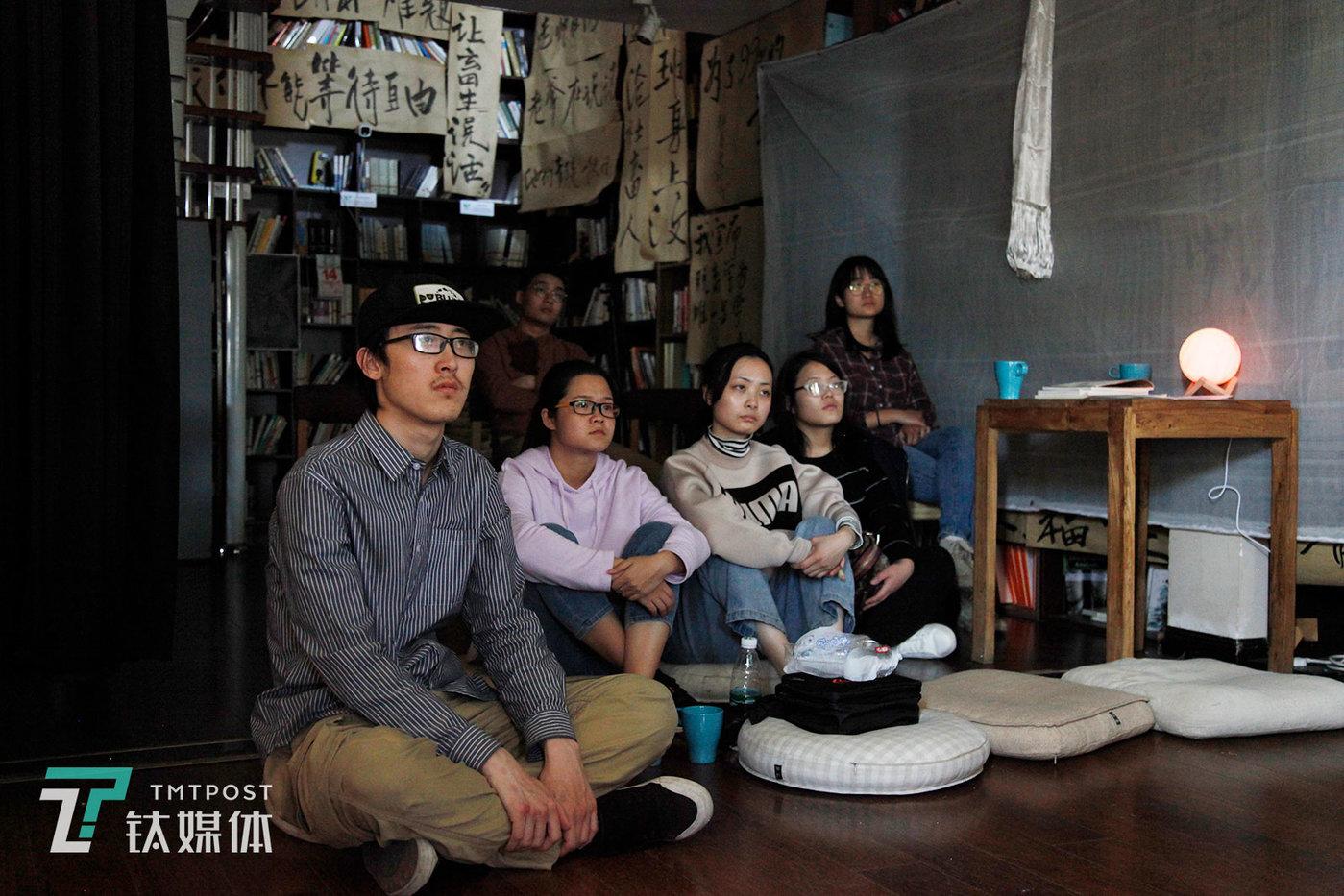 """4月14日,参展的观众在看社畜博物馆剧场放映的日本过劳死案例采访视频。有的观众表示""""看完视频觉得很压抑却又现实,会联想到自己的工作状态,觉得可怕。"""""""