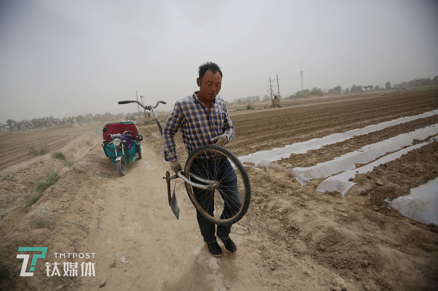May 18. Zhiming Xue squints his eyes to protect them against the gusts of sand spread by strong winds into the air of Lizhi Village.