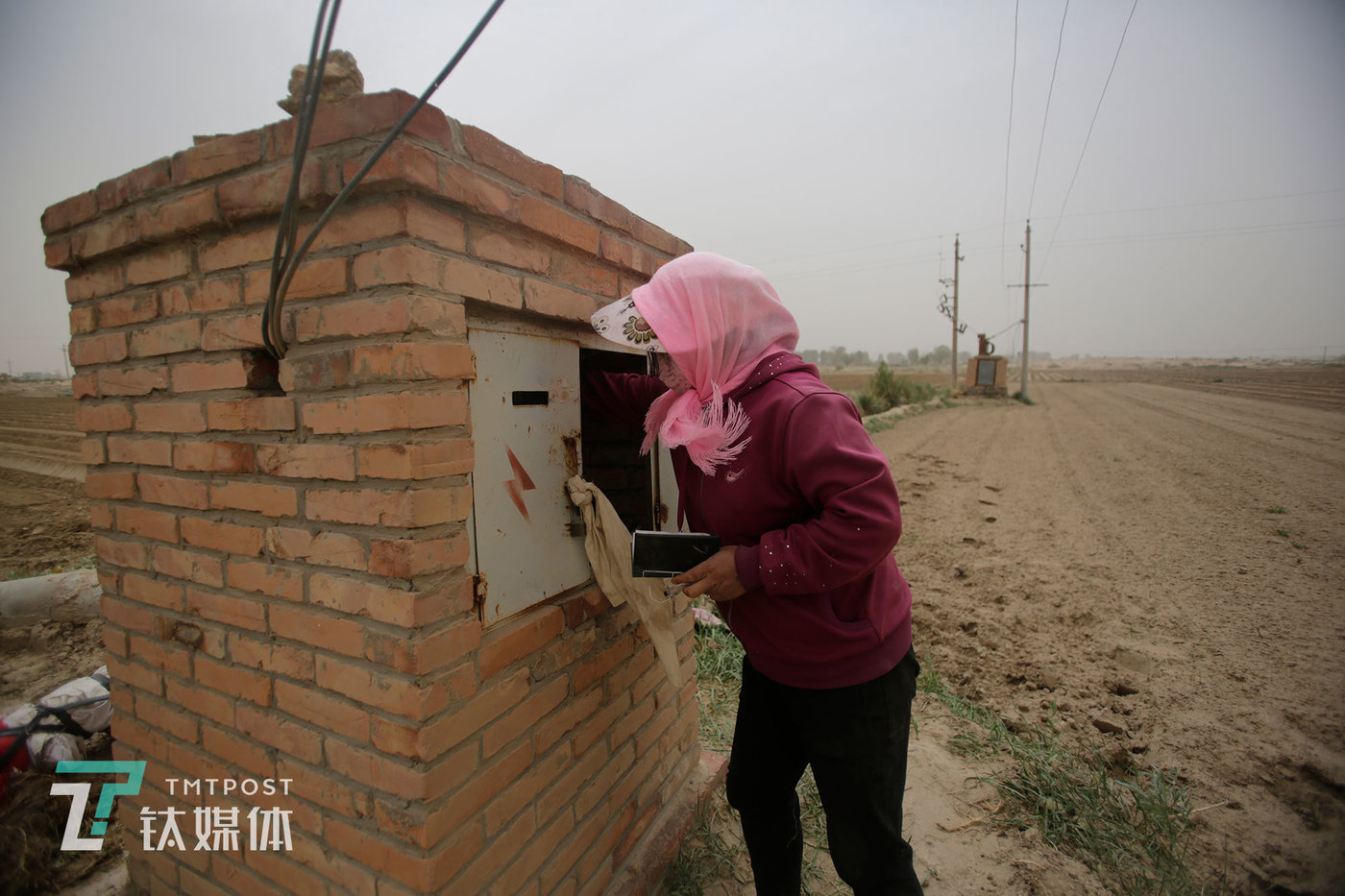 In Lizhi Village, a farmer switches the power on of a motor-pumped well that pumps water for irrigation.