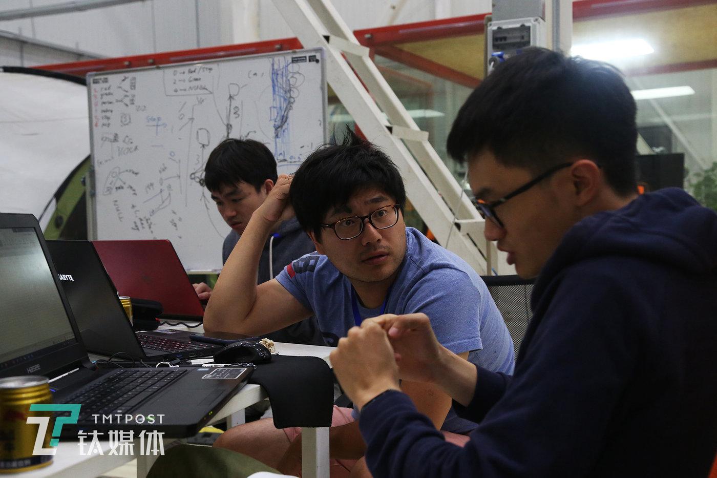 """2 DIFFICULT队""(下文简称D队)队长马臻在和队员讨论赛事方案比赛。D队由上海交通大学汽车工程学院博士后马臻带领的研究生团队、中国移动浙江公司AI算法工程师戚靓亮以及墨西哥深度神经网络学习算法工程师Fernando共6人组成。"