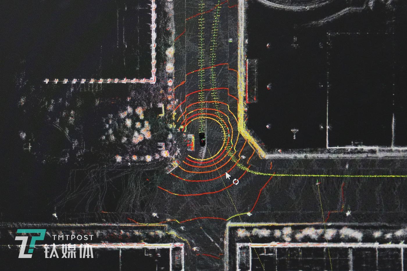 """路点录入阶段,D队车辆通过Velodyne 16线激光雷达D队车在行驶中,车内显示屏同步显示的""""激光雷达构建的点云高精地图""""。地图中间黑色矩形是车辆,。地图显示车周边环境,红圈为可视化道路路径,距离黑色车模型越近,颜色越亮,识别到的物体也会更清晰。绿色轨迹线条是为车辆行驶的线路。"""