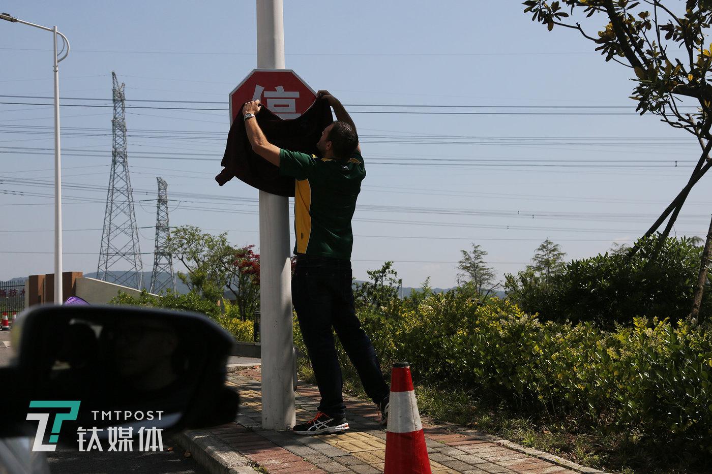 """2D队竞争对手 """"2EASY""""队的道路训练中,队队员用衣物遮挡停车标识来检测系统识别效果。"""