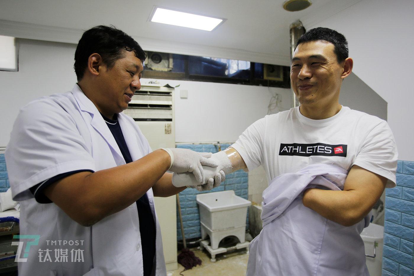 上海精博假肢临床中心主任沈杰伟在为倪敏成打石膏棉,以获取残肢的石膏模型来制作接受腔。